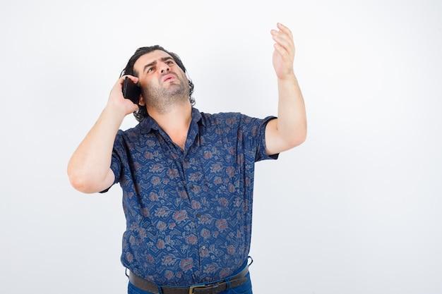 Reifer mann, der auf handy spricht, während hand in hemd hebt und nachdenklich aussieht. vorderansicht.