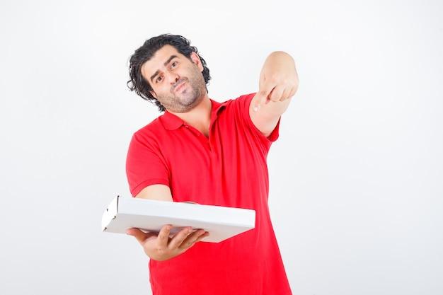 Reifer mann, der auf pizzaschachtel im roten t-shirt zeigt und selbstbewusst, vorderansicht schaut.