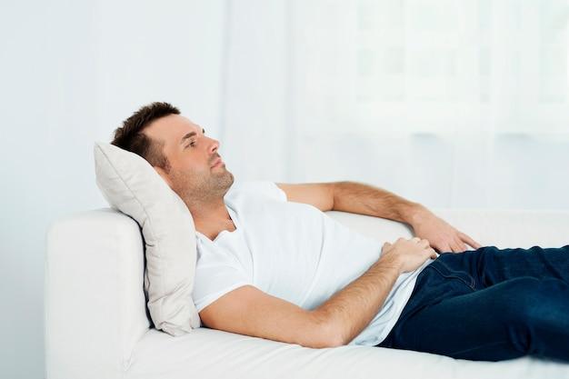 Reifer mann, der auf sofa entspannt