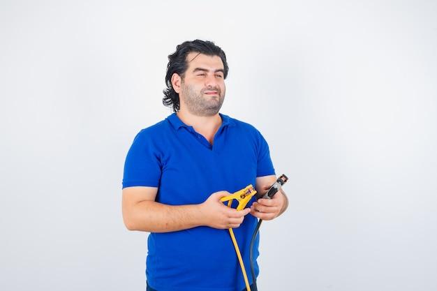 Reifer mann, der bauwerkzeuge im blauen t-shirt hält und nachdenklich schaut. vorderansicht.