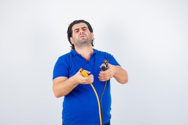 Reifer mann, der bauwerkzeuge im blauen t-shirt hält und ratlos, vorderansicht schaut.