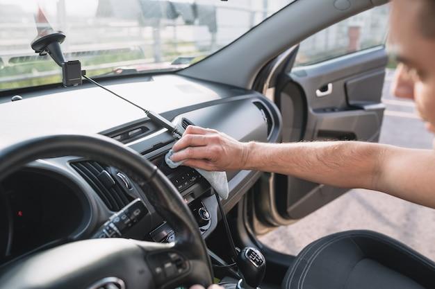 Reifer mann, der das armaturenbrett des autos mit einem tuch säubert. selektiver fokus auf die hand des mannes.