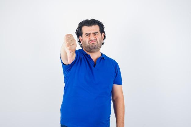 Reifer mann, der daumen unten im blauen t-shirt, jeans zeigt und enttäuscht schaut, vorderansicht.