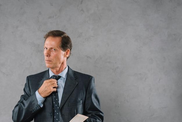 Reifer mann, der die bindung steht gegen grauen strukturierten hintergrund justiert
