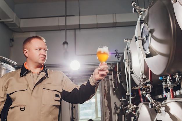 Reifer mann, der die qualität des handwerksbiers an der brauerei überprüft. inspektor, der an der alkoholherstellungsfabrik überprüft bier arbeitet. mann in der brennerei qualitätskontrolle des fassbiers überprüfend.