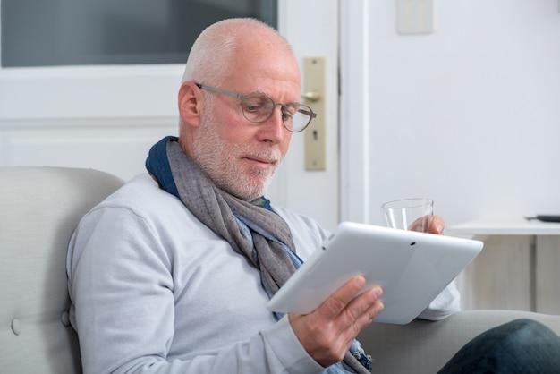Reifer mann, der digitale tablette auf sofa im wohnzimmer verwendet