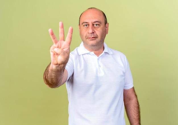 Reifer mann, der drei lokalisiert auf olivgrün zeigt