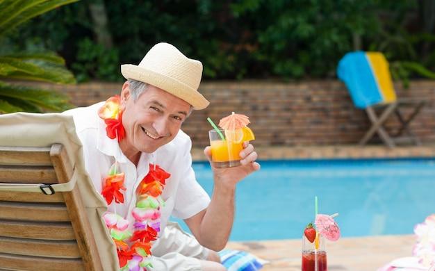 Reifer mann, der ein cocktail neben dem swimmingpool trinkt