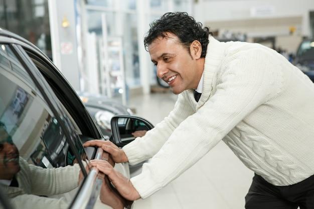 Reifer mann, der ein neues auto im händlersalon wählt