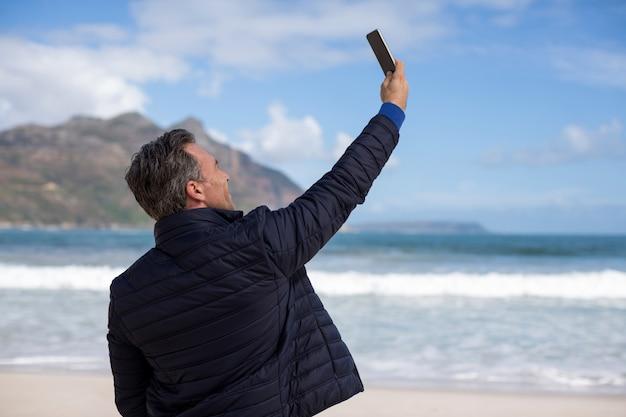 Reifer mann, der ein selfie vom handy am strand nimmt