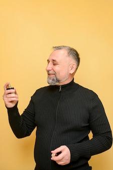 Reifer mann, der eine flasche parfüm hält
