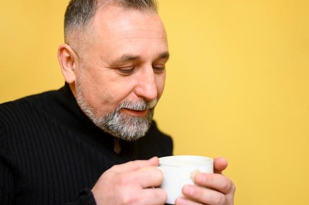 Reifer mann, der eine tasse tee hält