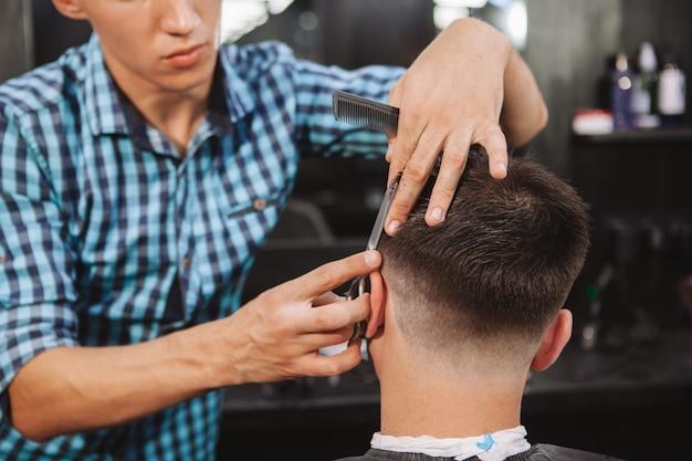 Reifer mann, der einen neuen haarschnitt am friseursalon erhält