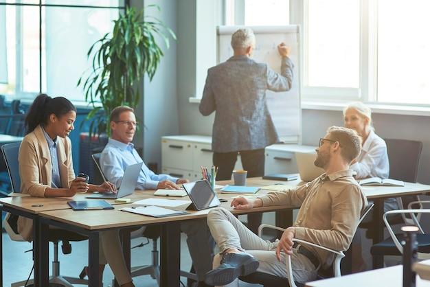 Reifer mann, der etwas an der weißen tafel schreibt und ein brainstorming-meeting mit dem team in der