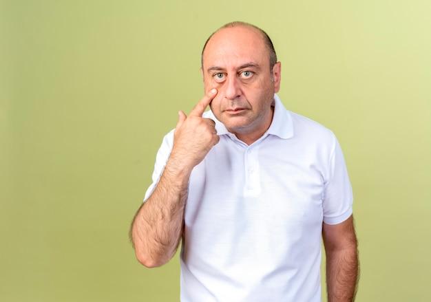 Reifer mann, der finger auf auge lokalisiert auf olivgrüner wand setzt