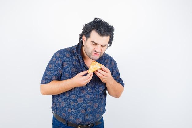 Reifer mann, der gebäckprodukt im hemd betrachtet und hungrig schaut. vorderansicht.