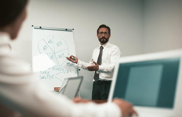 Reifer mann, der geschäftspräsentation oder konferenz macht. sprecher mann steht in der nähe von whiteboard mit