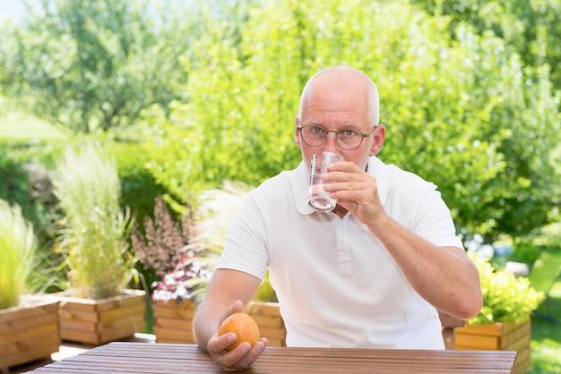 Reifer mann, der glas wasser auf der terrasse trinkt