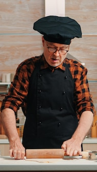Reifer mann, der hausgemachte pizza zu hause zubereitet. glücklicher älterer koch mit knochen, der mit holznudelholz rohe zutaten knetet, um traditionelle kekse zu backen, mehl auf dem tisch zu bestreuen und zu sieben.