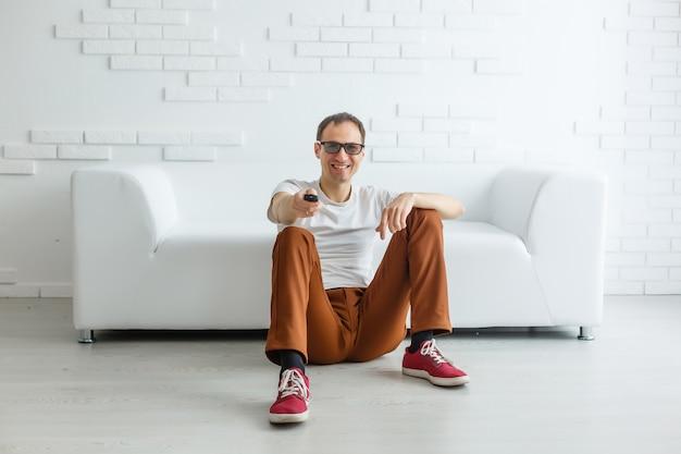 Reifer mann, der im couch-aufpassenden fernsehen sitzt