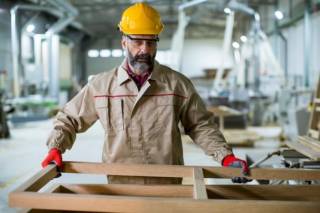 Reifer mann, der in der möbelfabrik arbeitet