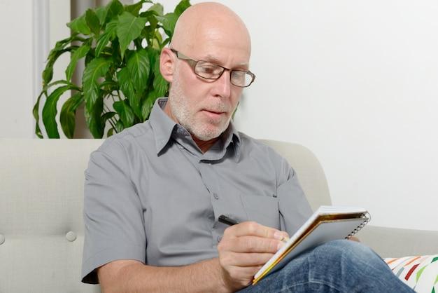 Reifer mann, der in einem sofa sitzt und notizen macht