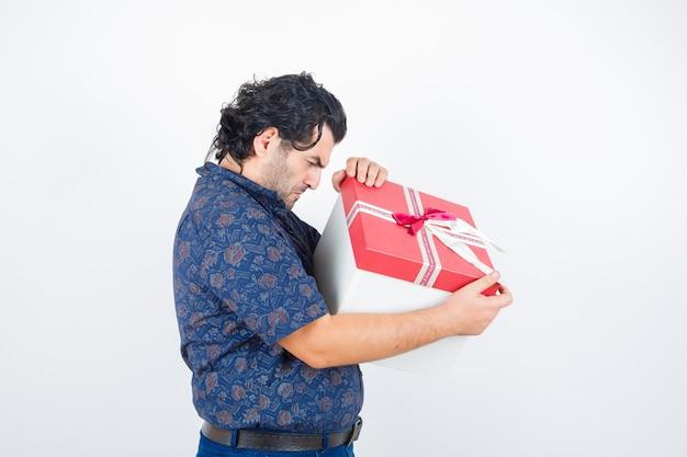 Reifer mann, der in geschenkbox im hemd schaut und konzentriert schaut. vorderansicht.