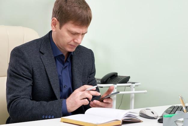 Reifer mann, der in seinem büro sitzt, sms auf smartphone