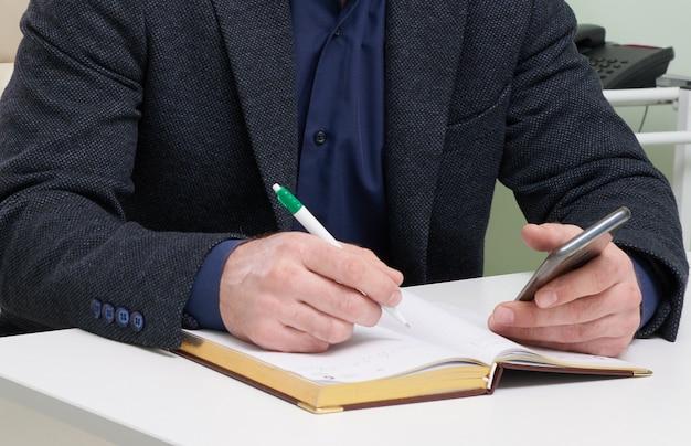 Reifer mann, der in seinem büro sitzt und in notizblock schreibt