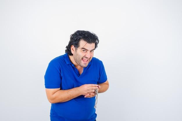 Reifer mann, der kette im blauen t-shirt hält und glücklich schaut. vorderansicht.