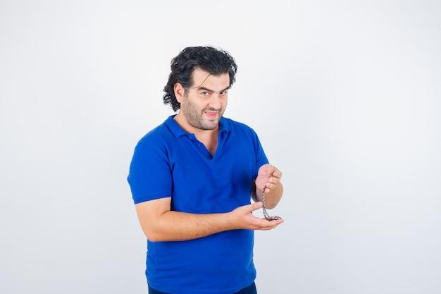 Reifer mann, der kette im blauen t-shirt hält und nachdenklich, vorderansicht schaut.