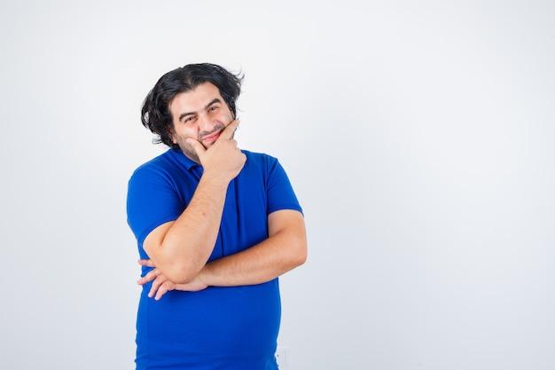 Reifer mann, der kinn auf handfläche lehnt, über etwas im blauen t-shirt, in den jeans nachdenkt und nachdenklich, vorderansicht schaut.