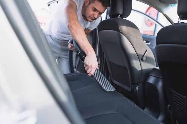Reifer mann, der mit staubsaugerinnenraum des luxusautos säubert. selektiver fokus auf die hand des mannes.