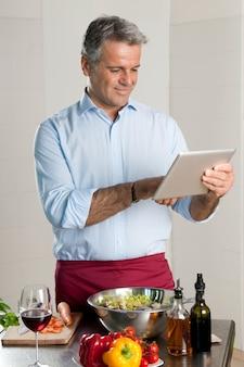 Reifer mann, der nach einem rezept auf einem digitalen tablett beim kochen zu hause küche sucht