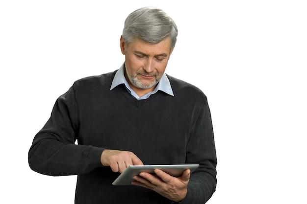 Reifer mann, der netz auf computertablett surft. mann mit grauem haar, das sein neues computertablett auf weiß untersucht. Premium Fotos