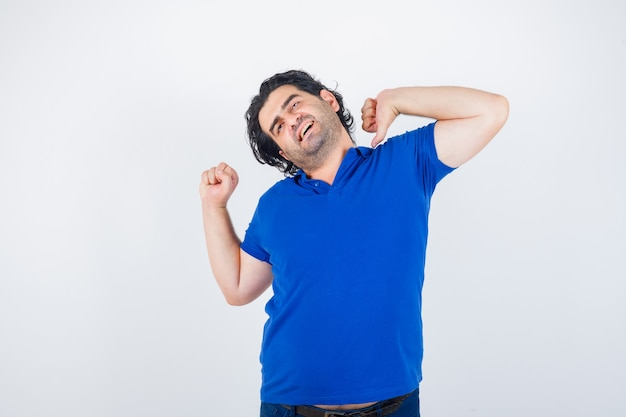 Reifer mann, der oberkörper im blauen t-shirt streckt und entspannt, vorderansicht schaut.