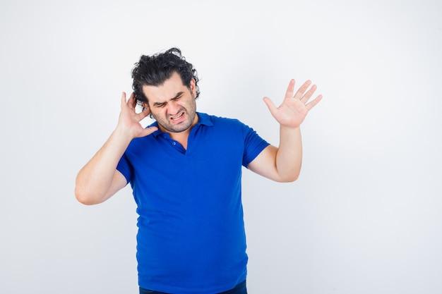 Reifer mann, der ohr mit finger einsteckt, stoppgeste in blauem t-shirt zeigt und genervt aussieht. vorderansicht.