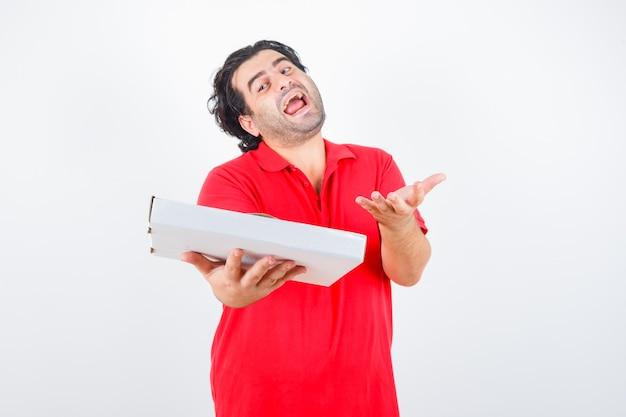 Reifer mann, der pizzaschachtel hält, während hand in fragender geste im roten t-shirt streckt und glückliche vorderansicht schaut.