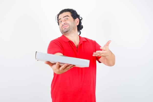 Reifer mann, der pizzaschachtel im roten t-shirt präsentiert und niedlich, vorderansicht schaut.