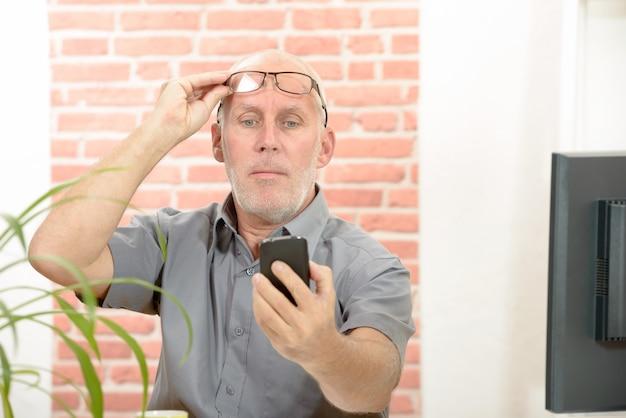 Reifer mann, der probleme hat, telefonschirm wegen der anblickprobleme zu sehen