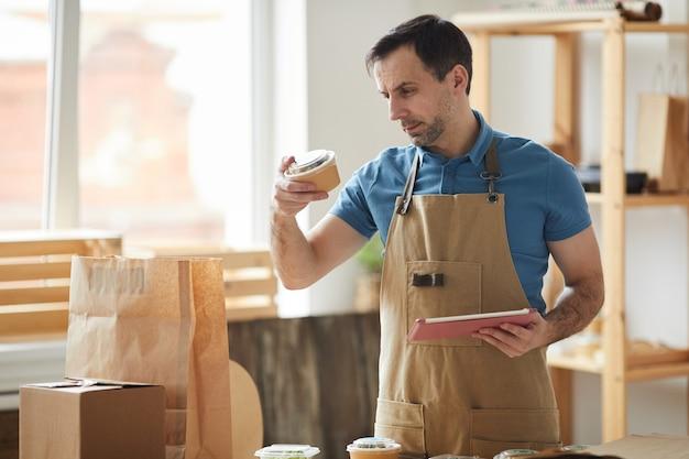 Reifer mann, der schürzenverpackungsaufträge trägt, während er durch holztisch, lebensmittel-lieferservice-arbeiter steht