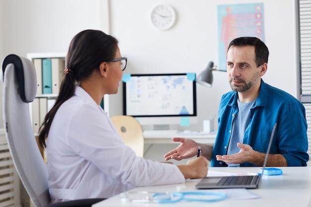 Reifer mann, der seinem arzt gegenüber sitzt und über seine beschwerden über die gesundheit im krankenhaus berichtet