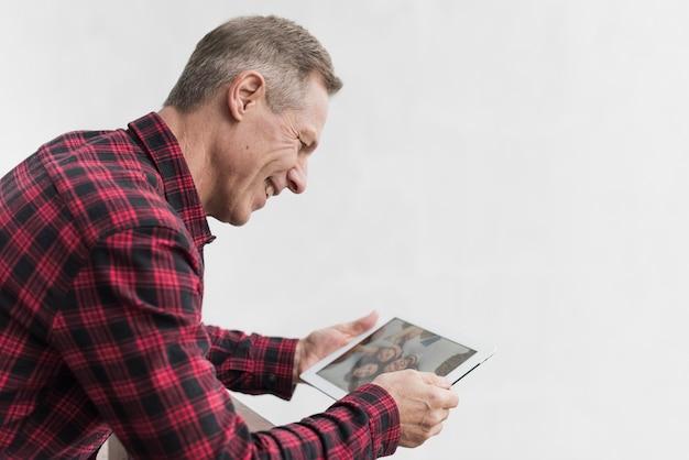 Reifer mann der seitenansicht, der auf fotos mit seinen kindern und enkelkindern schaut