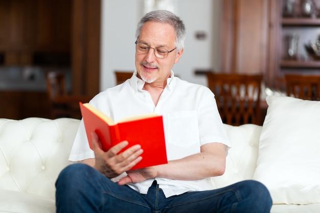 Reifer mann, der sich entspannt, während er ein buch auf einem sofa zu hause liest