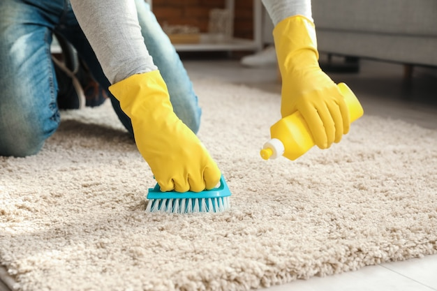 Reifer mann, der teppich zu hause, nahaufnahme reinigt