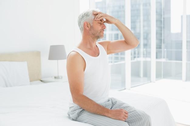 Reifer mann, der unter kopfschmerzen im bett leidet