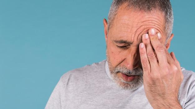 Reifer mann, der unter kopfschmerzen leidet