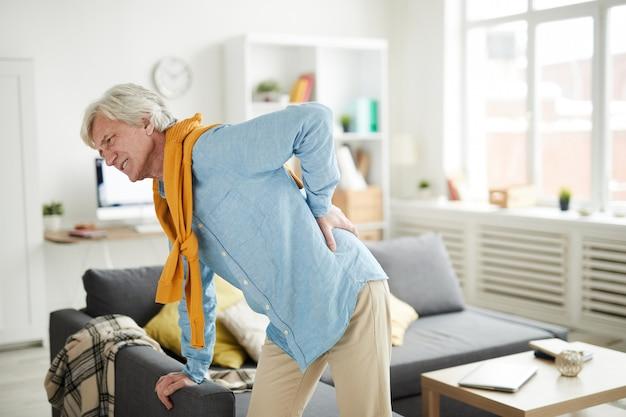 Reifer mann, der unter rückenschmerzen leidet