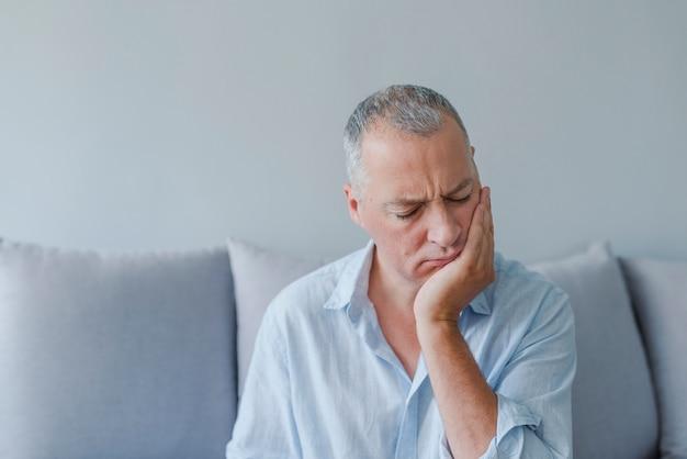 Reifer mann, der unter zahnschmerz, karies leidet