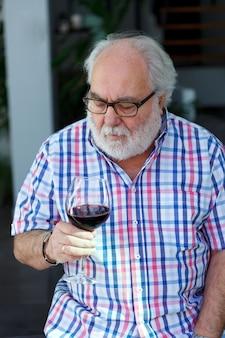 Reifer mann, der wein trinkt
